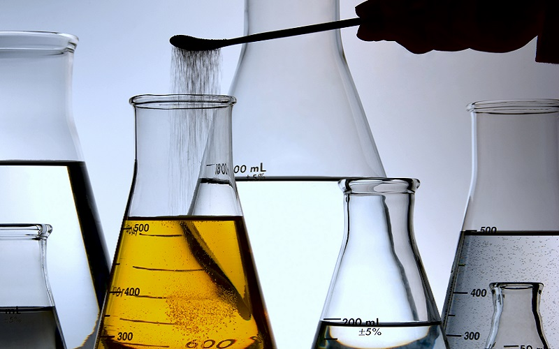Chemist Adding Powder to Lab Flask